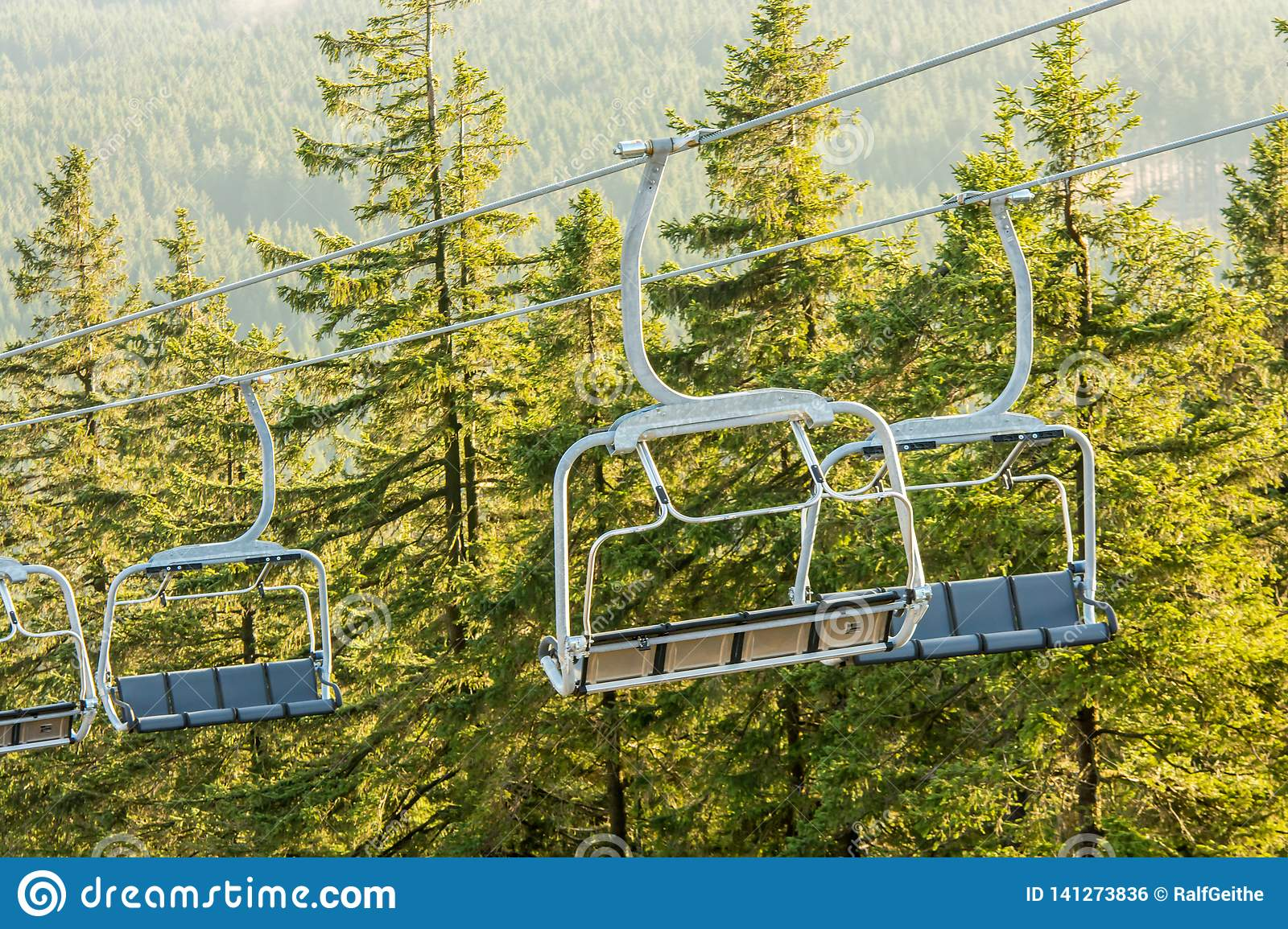 Empty chairlift with big gondolas in a forest area