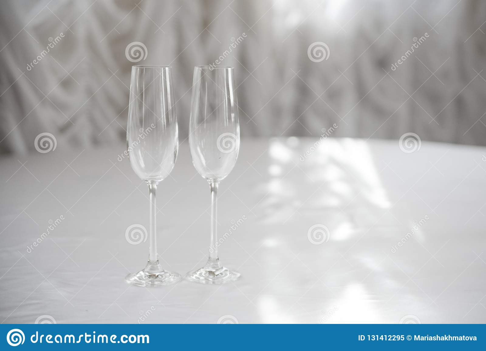 Empty champagne glasses on a white tablecloth against the background of white curtains in backlight