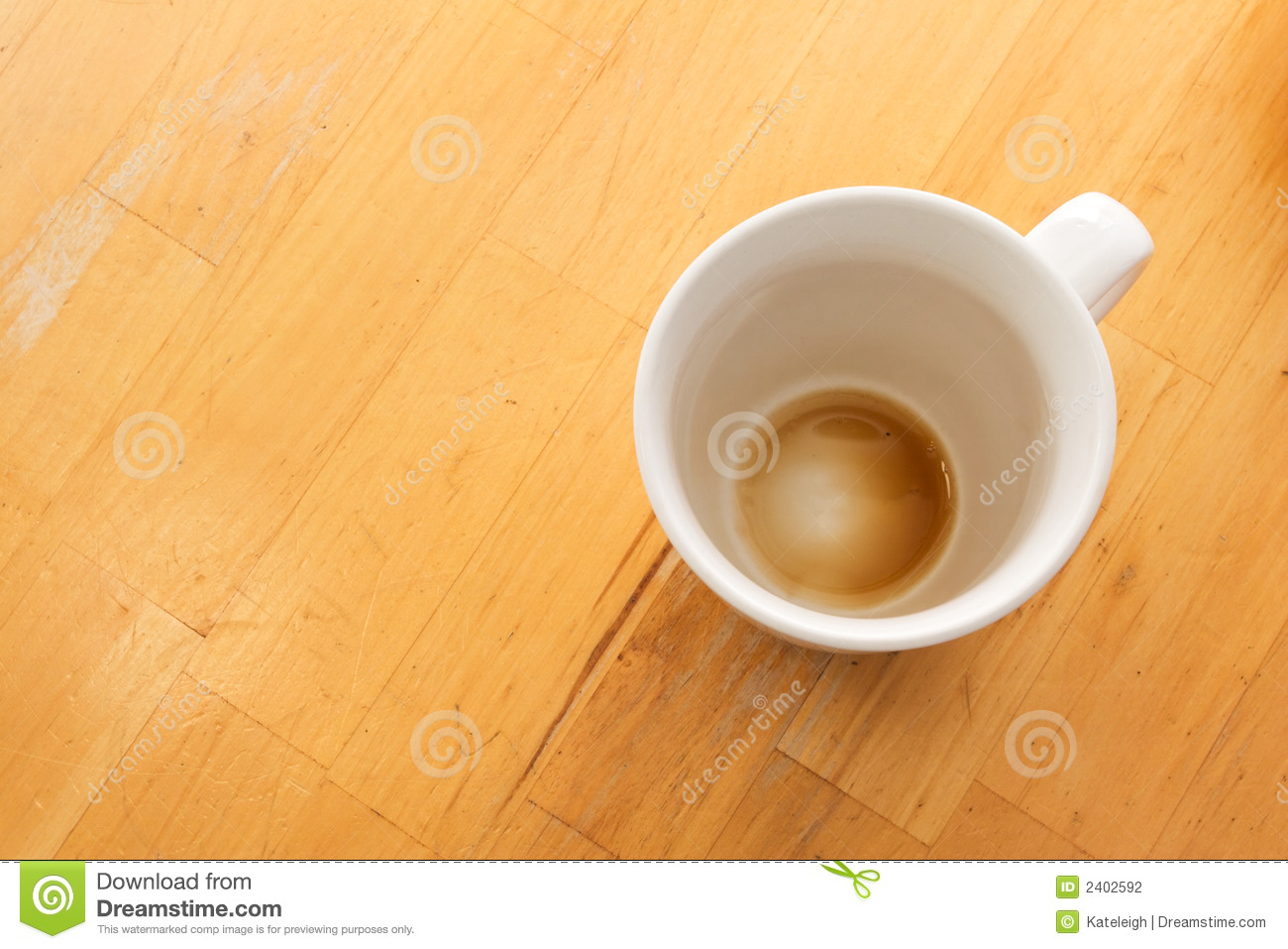 An empty cup of coffee viewed from above on a wooden table.