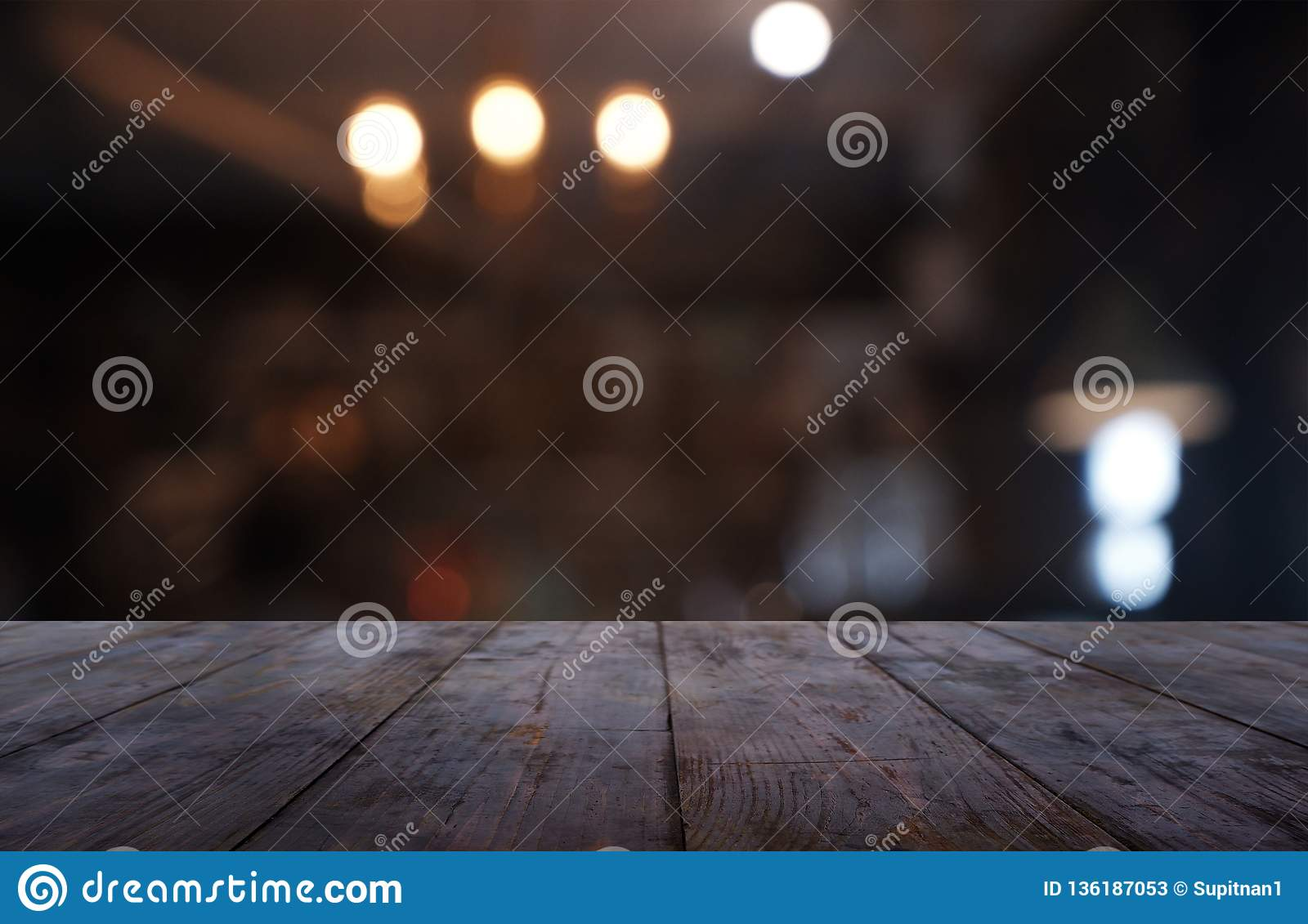 Empty dark wooden table in front of abstract blurred background of cafe and coffee shop interior. can be used for display or
