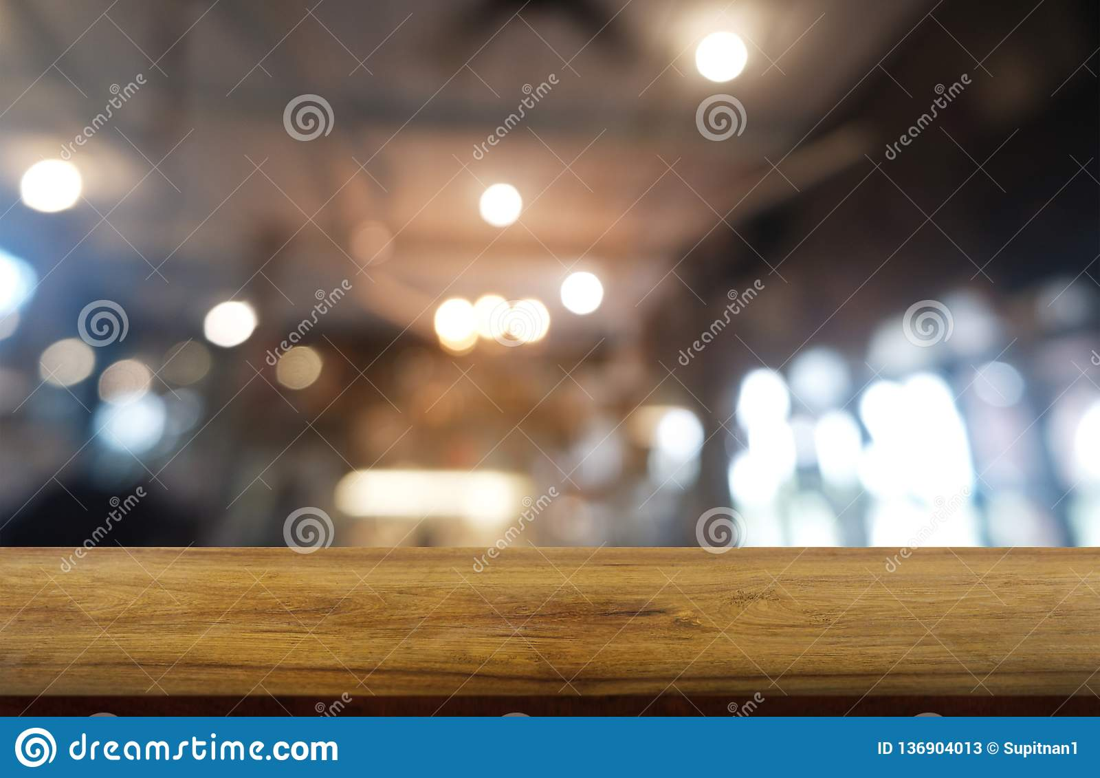 Empty dark wooden table in front of abstract blurred background of restaurant, cafe and coffee shop interior. can be used for