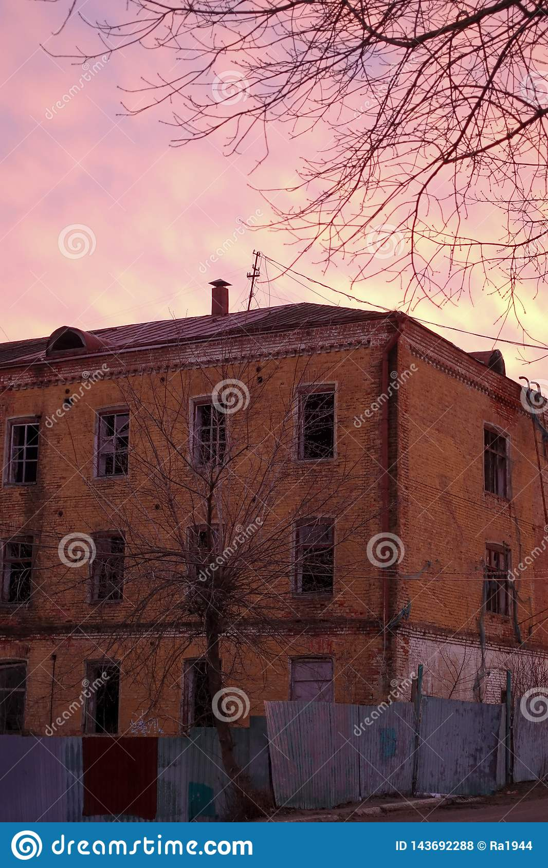 Empty destroyed building with broken windows. Pink sky Sunset. Photo in red colors. The oppressive atmosphere of destruction.