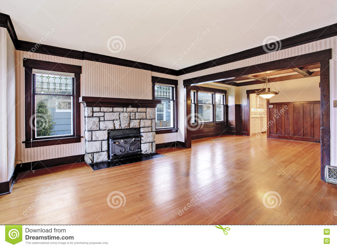 Empty family room with antique stone fireplace and for Wood floor up to fireplace