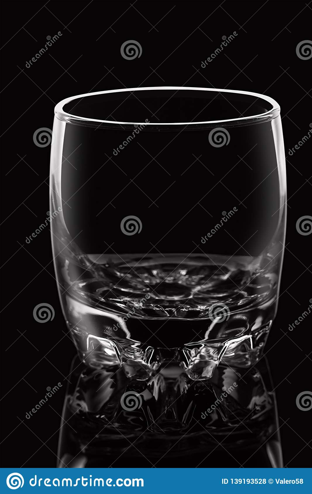 Empty glass on black background with highlights.