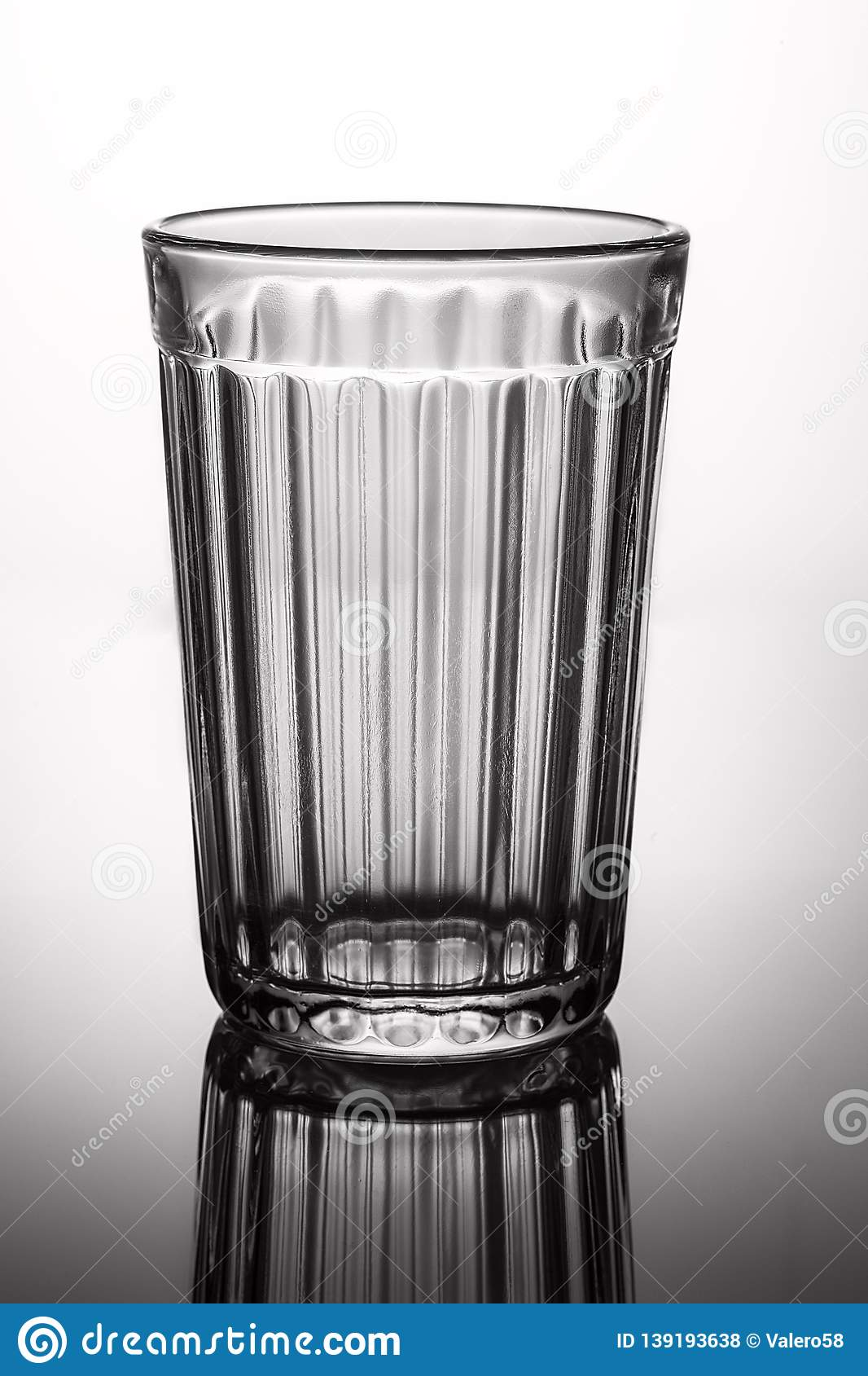 Empty glass on gray background with highlights.