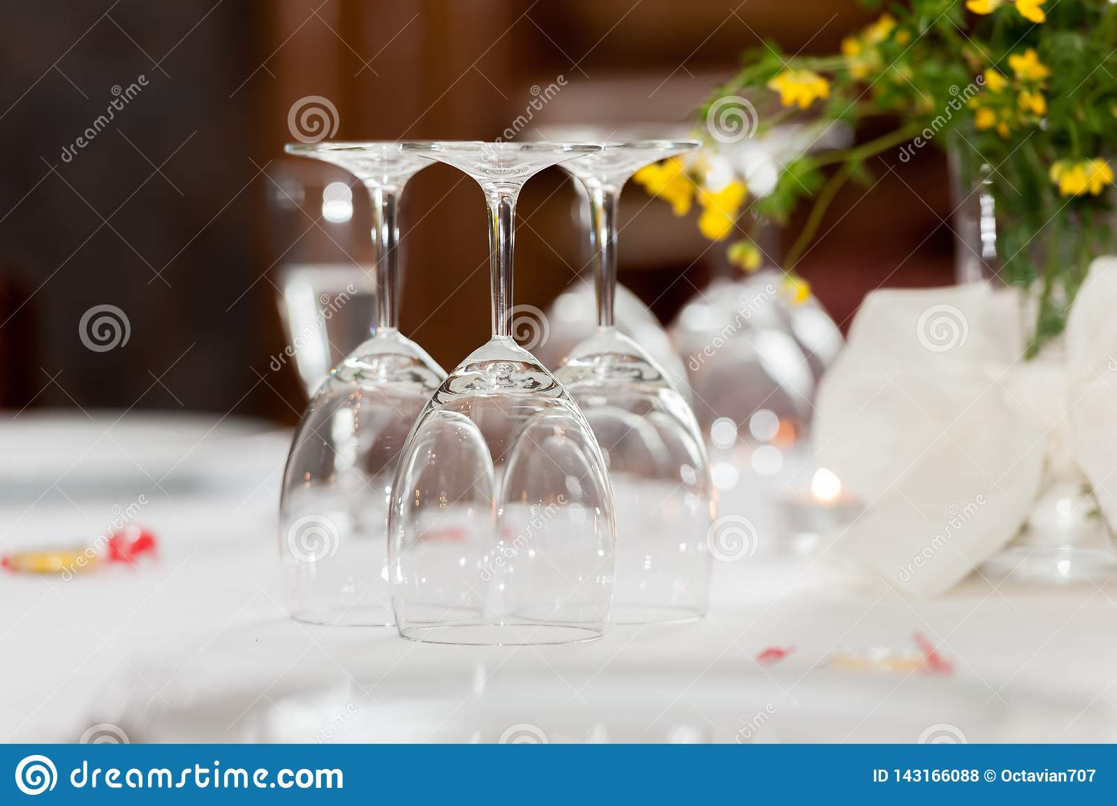 Empty glasses on table in restaurant with floral decoration