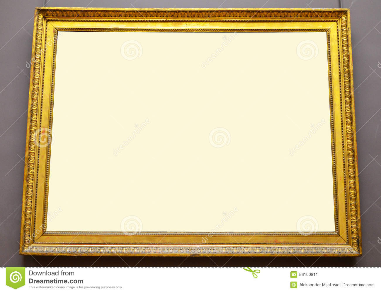 Empty golden picture frame hanging on wall
