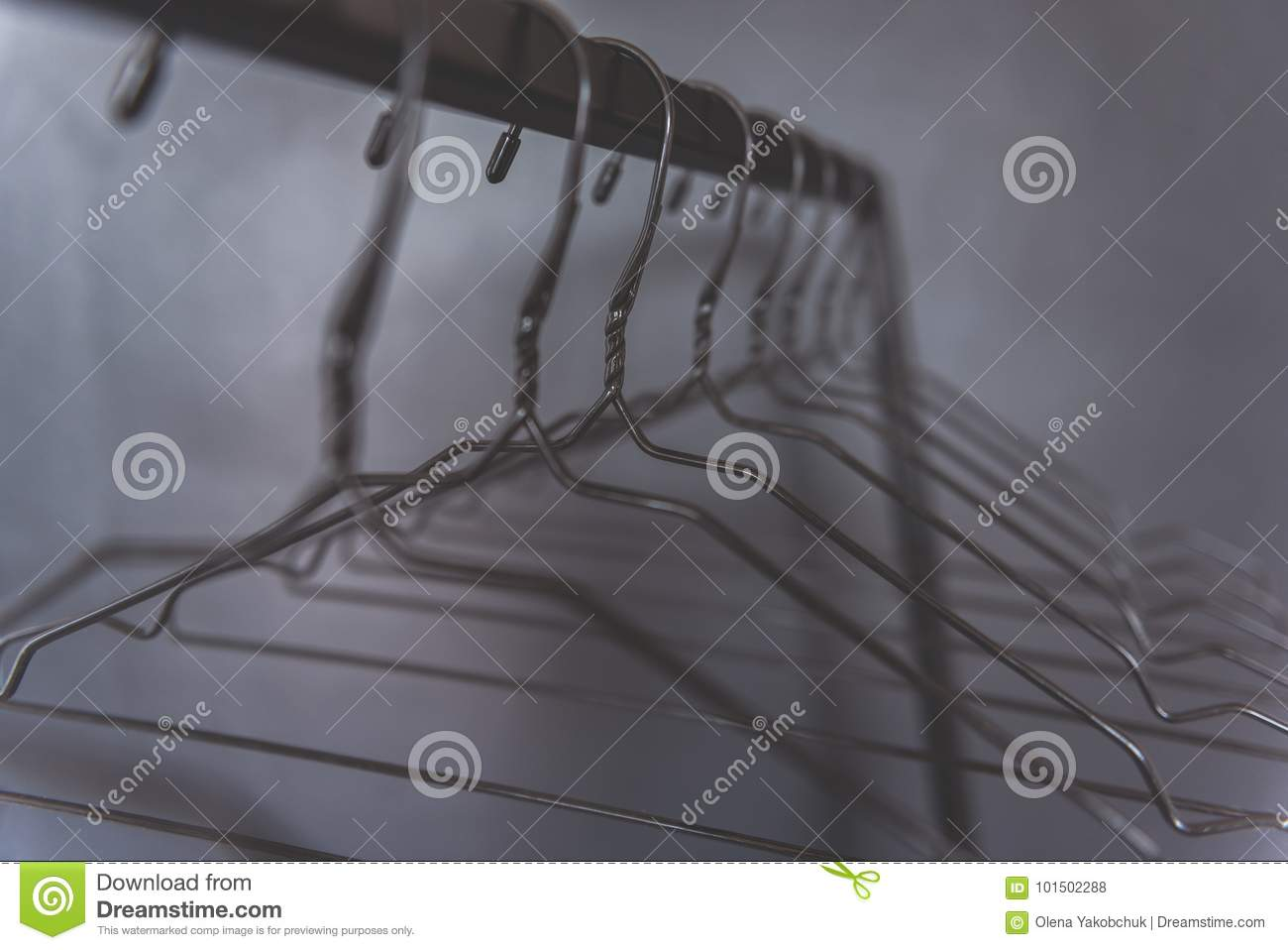 1f2b0d6e962 Empty hangers are hanging at cross-bar near grey wall. Close up of shaped  wires. Copy space. Nobody