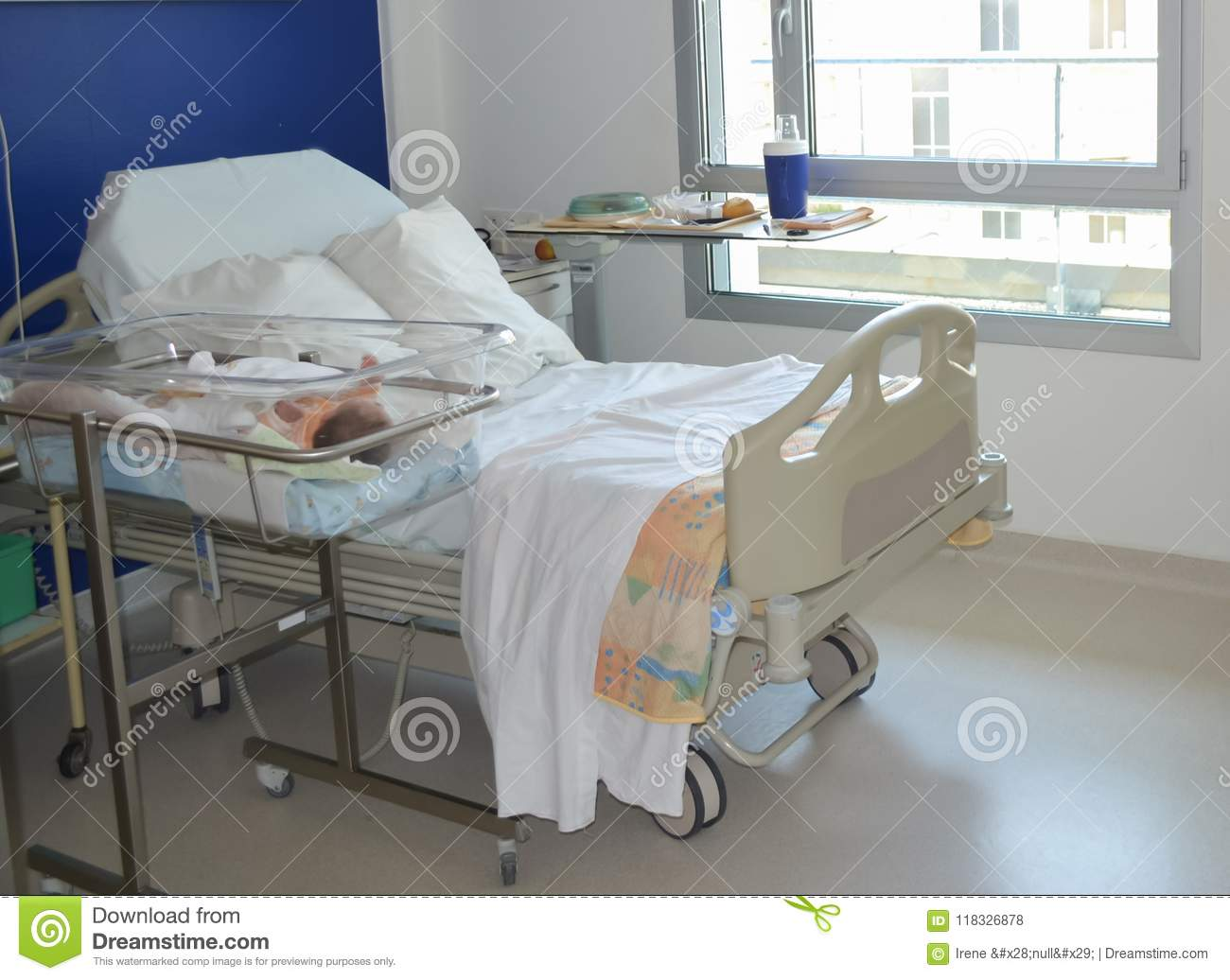 Empty Hospital Bed And Newborn Baby Near The Bed Stock Photo
