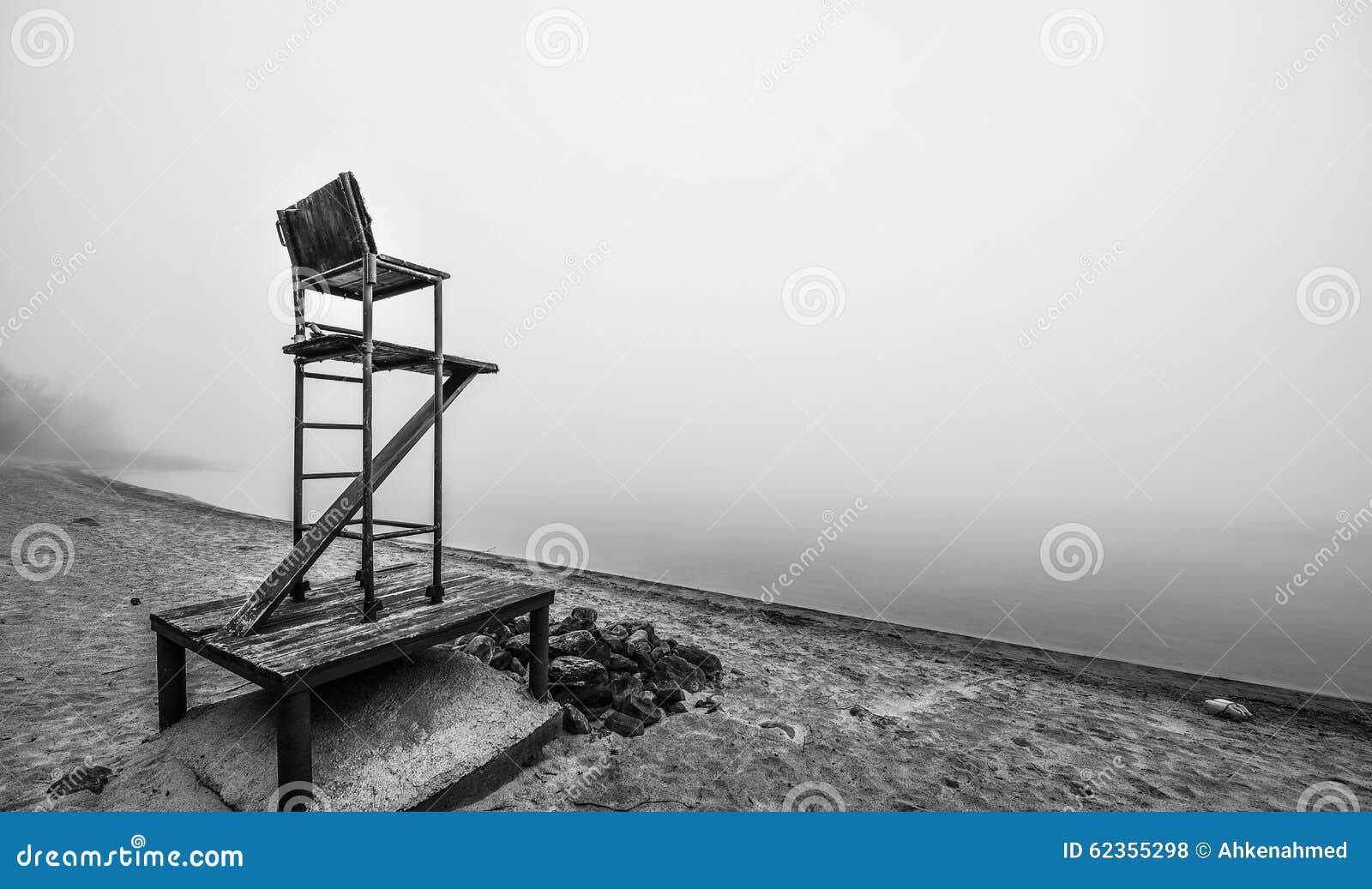 Empty lifeguard chair on the beach on a foggy morning.