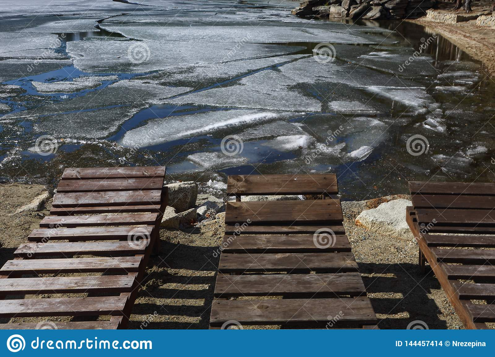 Empty loungers on the beach while ice on the lake