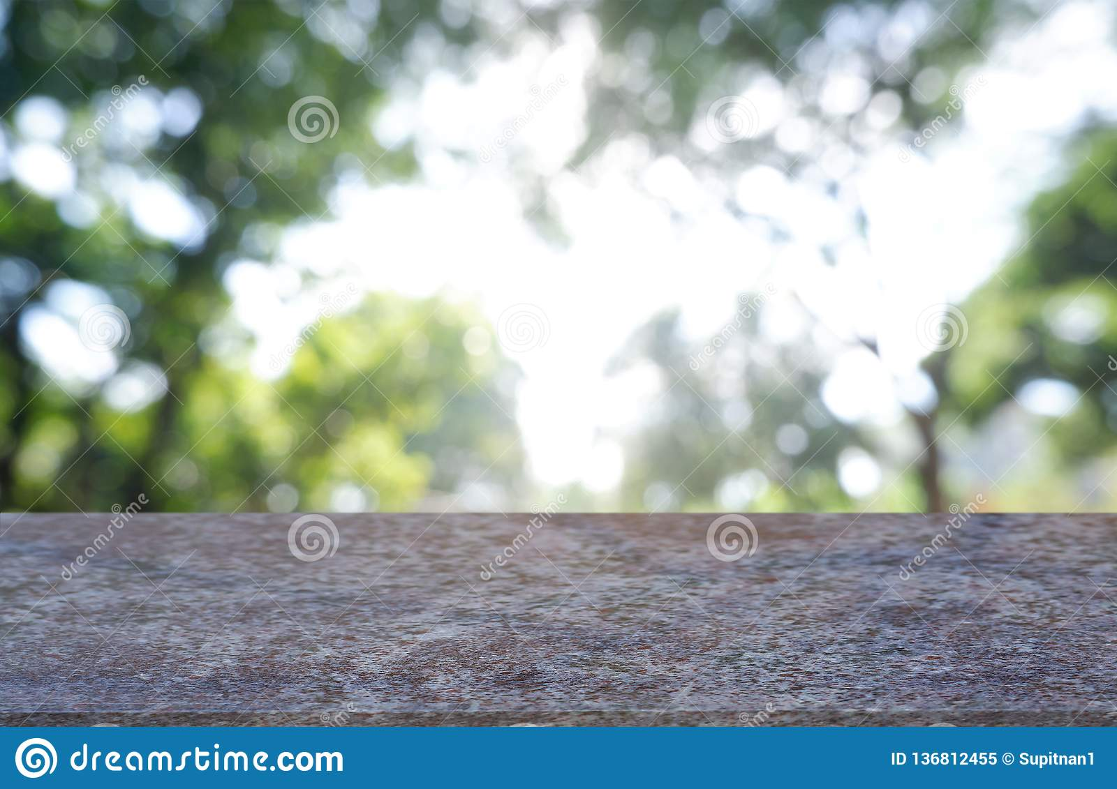 Empty marble stone. table in front of abstract blurred green of garden and trees.background. For montage product display or design