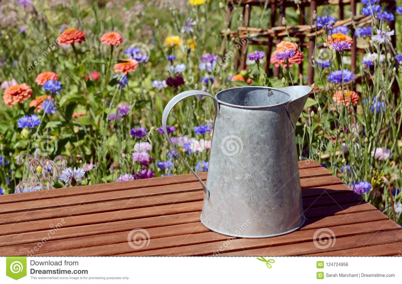 Empty Metal Pitcher On A Table In A Flower Garden Stock ...