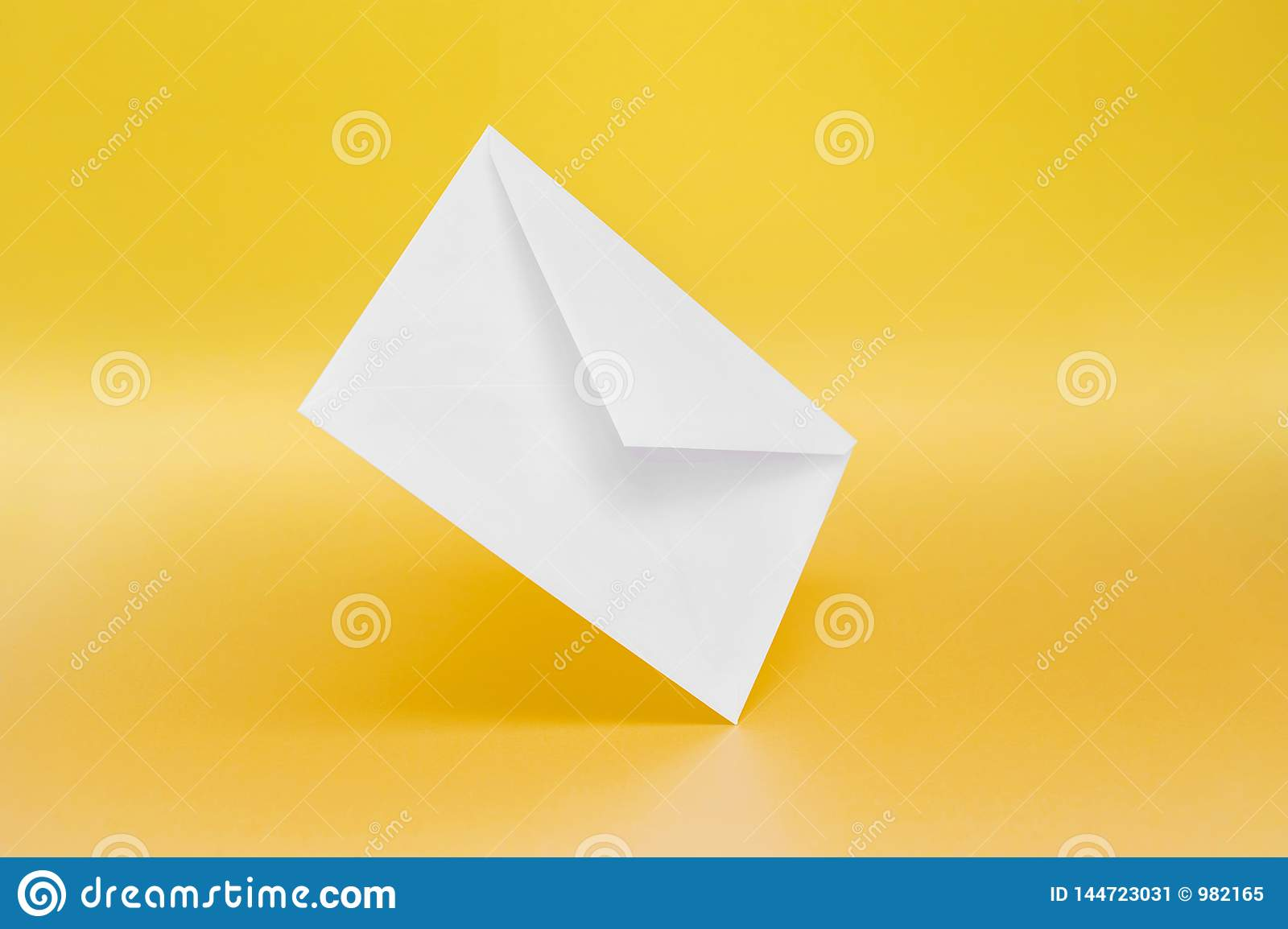 Empty paper envelope on yellow background