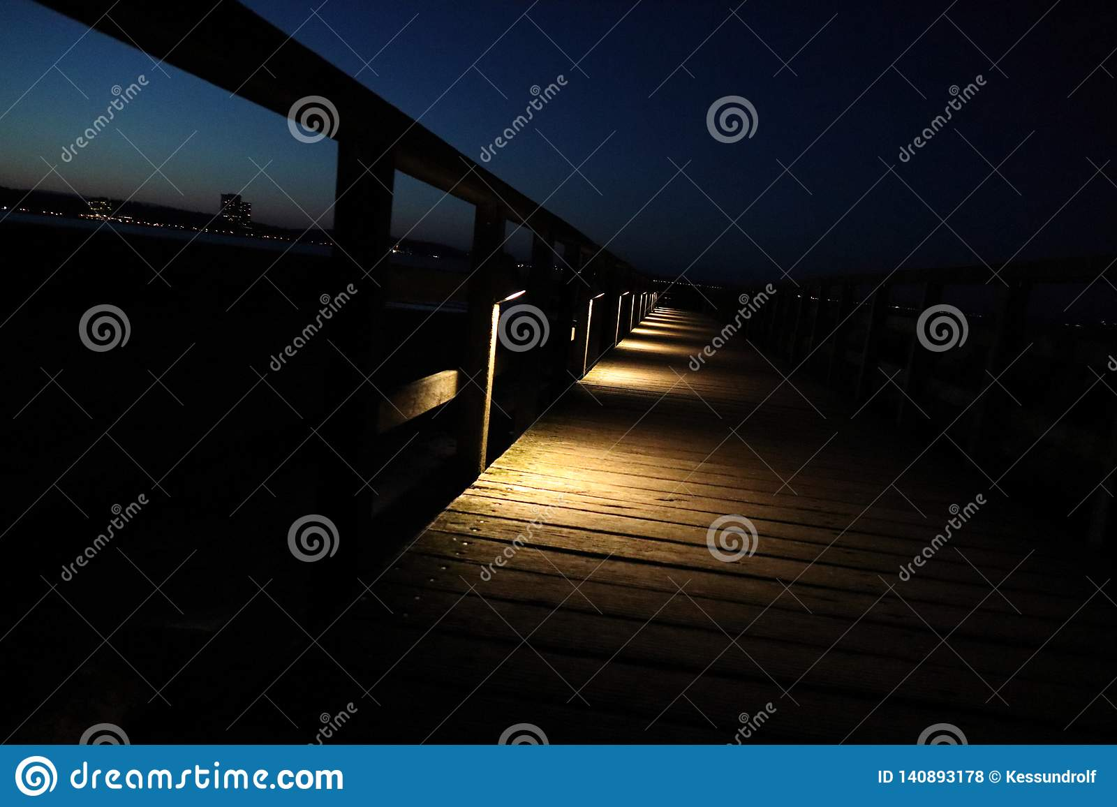 Empty pedestrian bridge by night with lamps and calm sea