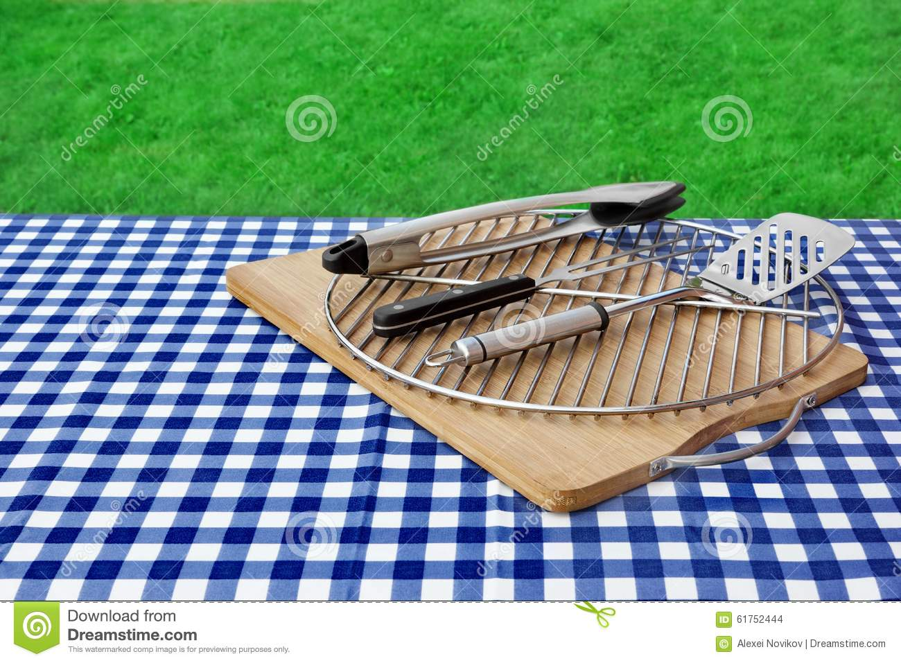 Empty picnic table checkered tablecloth grid bbq grill
