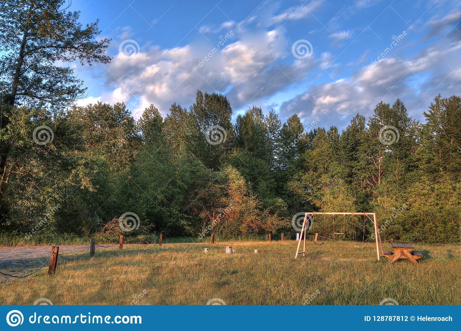 Empty Picnic Table And Swing Set In The Golden Hour Stock Photo