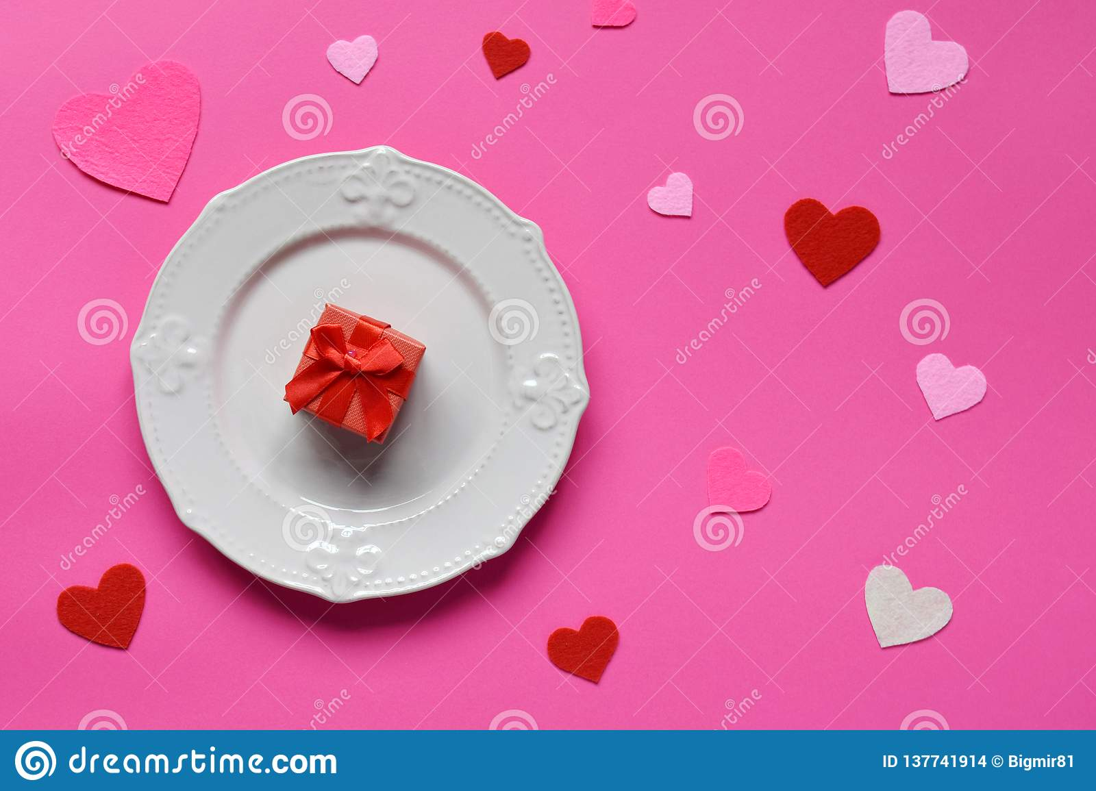 Empty pink plate, felt hearts and red gift on pink background. St. Valentine& x27;s Day concept. Top view, flat lay. Copy space