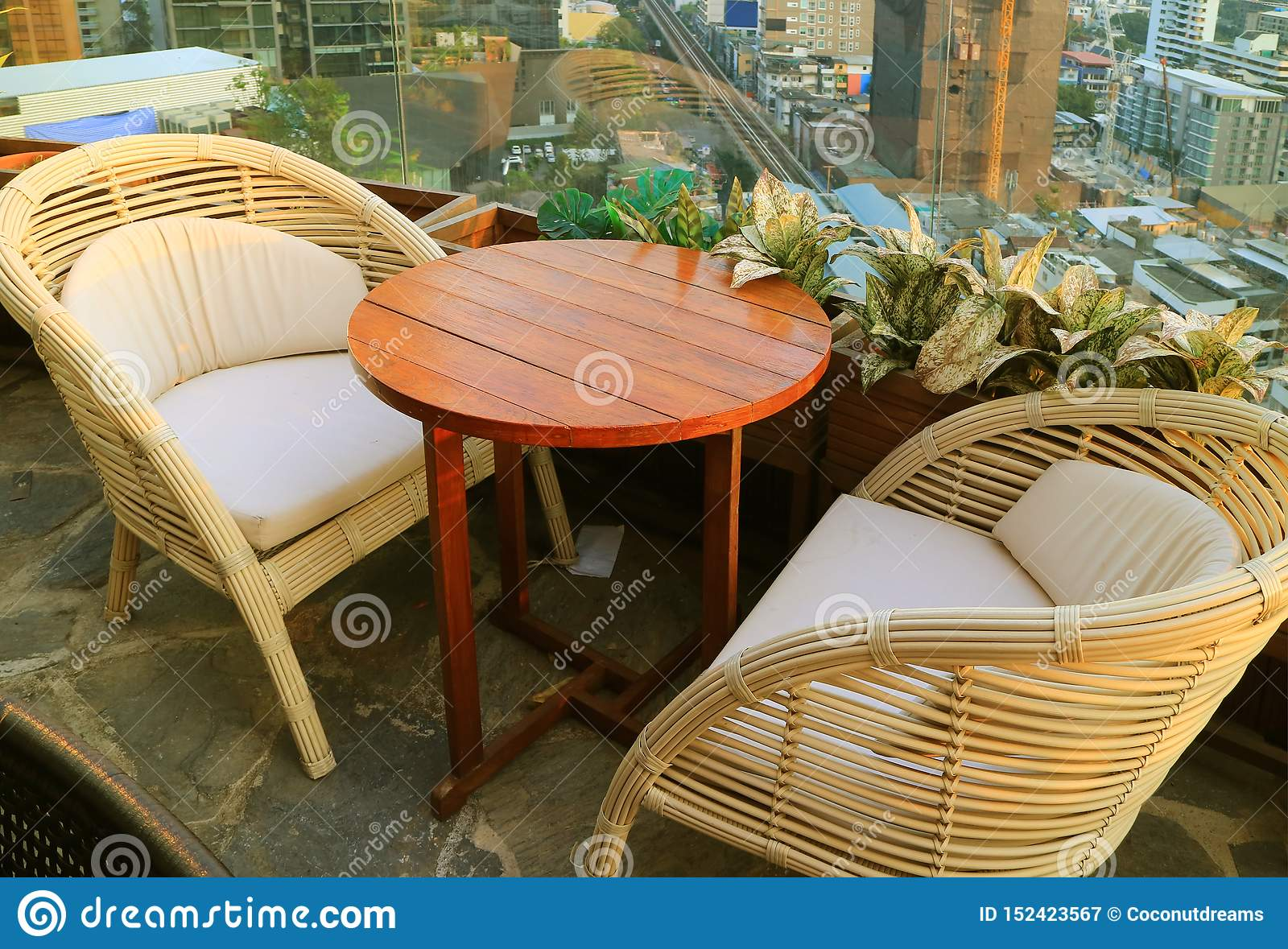 Empty Rattan Chairs With Round Table At The Rooftop Terrace Stock