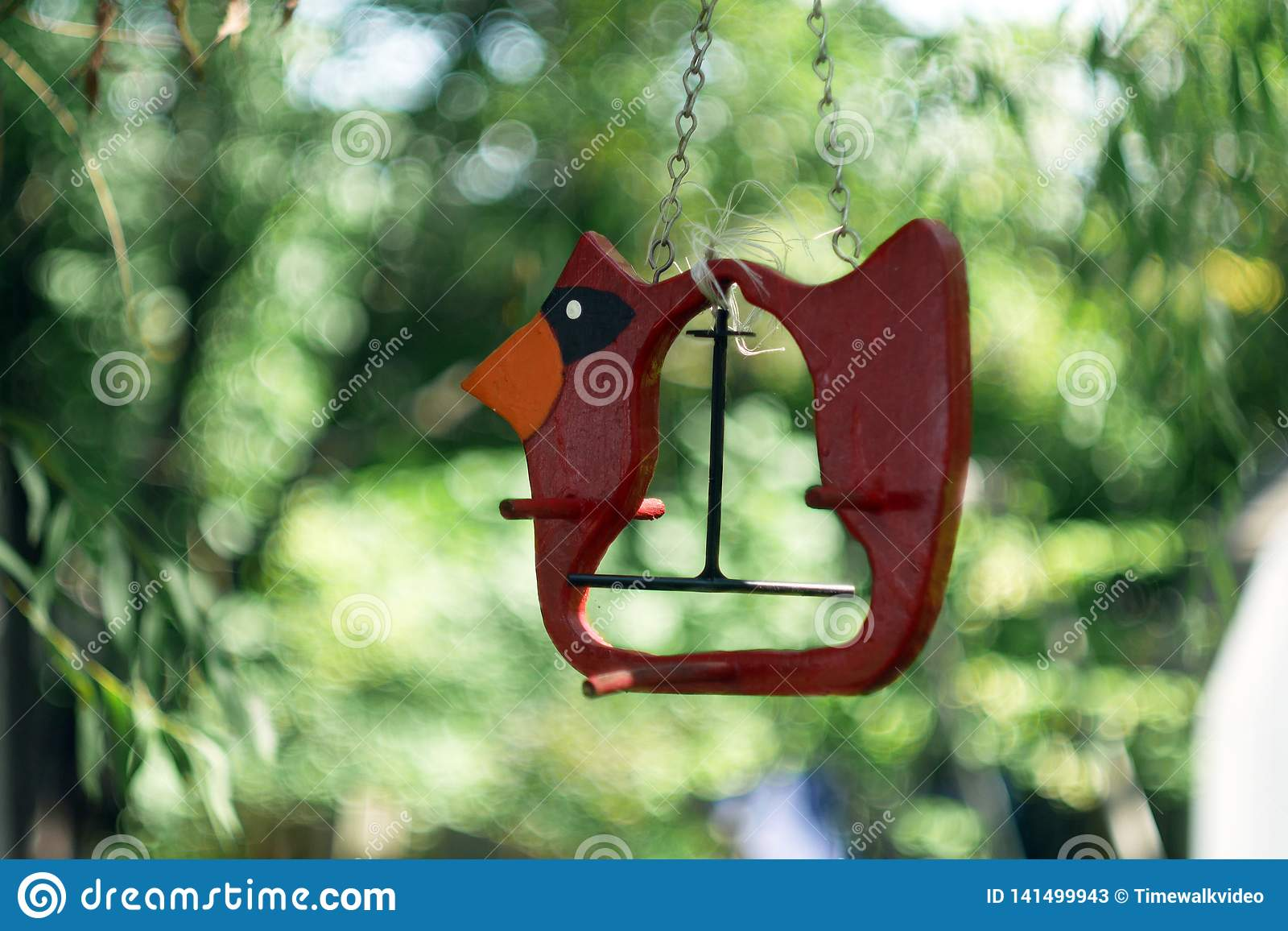 Empty Red bird feeder in the backyard with dreamy bokeh background