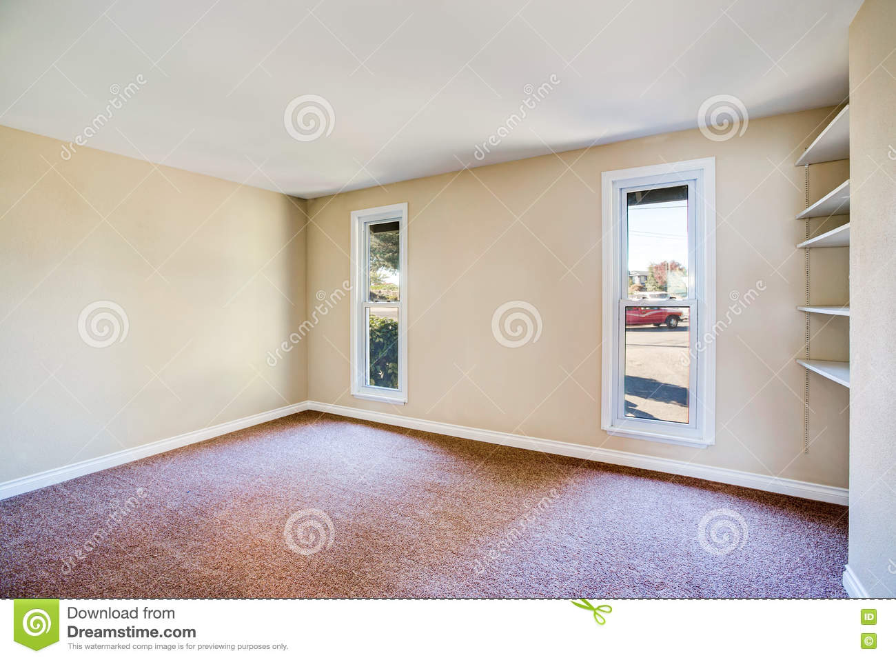 Empty Room Interior With Brown Carpet And Light Beige Walls