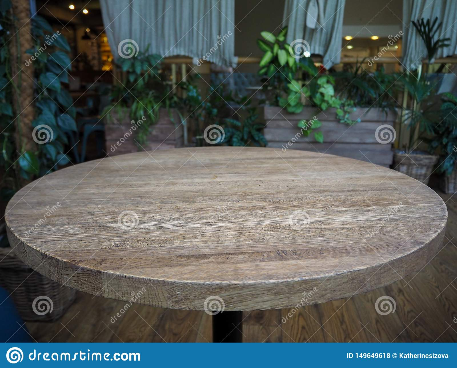 Empty round wooden table in a restaurant on the background of green plants