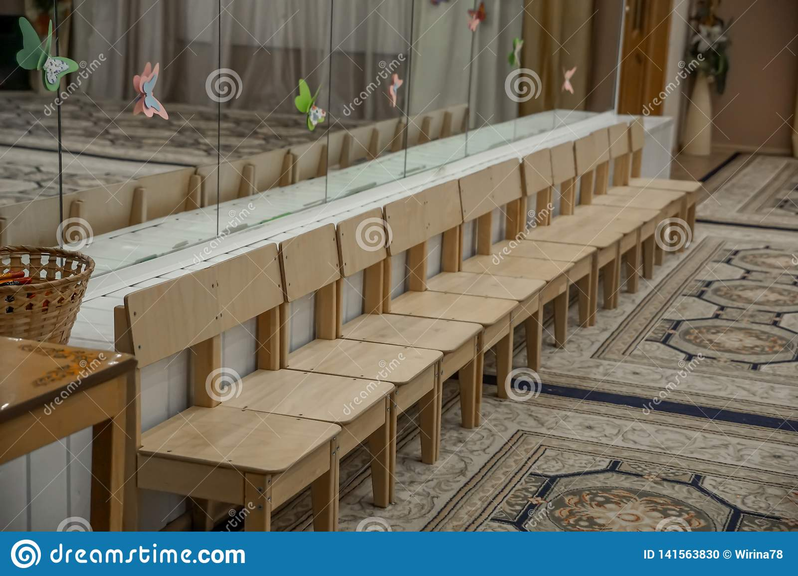 Empty row of wood children chairs in music room before celebration in music-hall waiting party