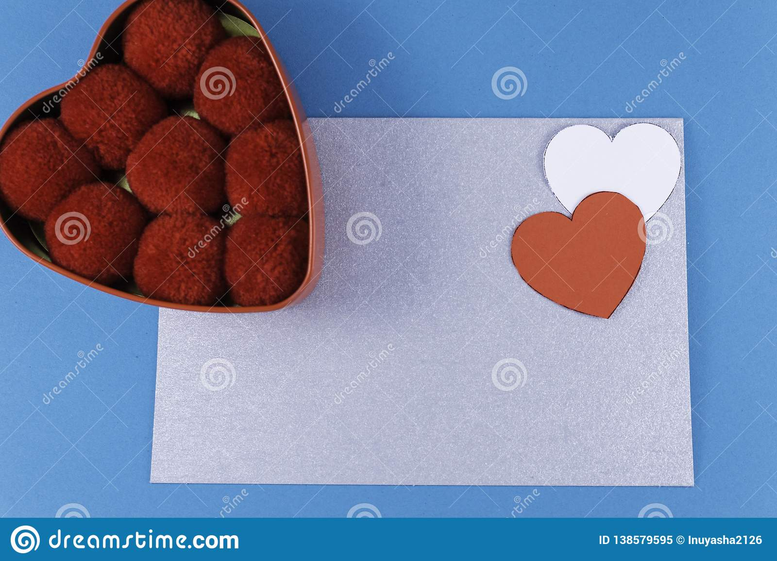 empty silver letter with two hearts of red and white color box next to balls of cotton red on a blue background