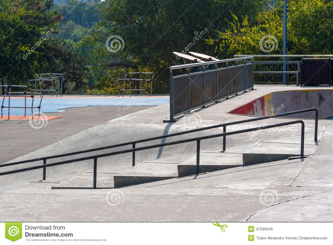 Empty skatepark at noon with ramps and grind rails.