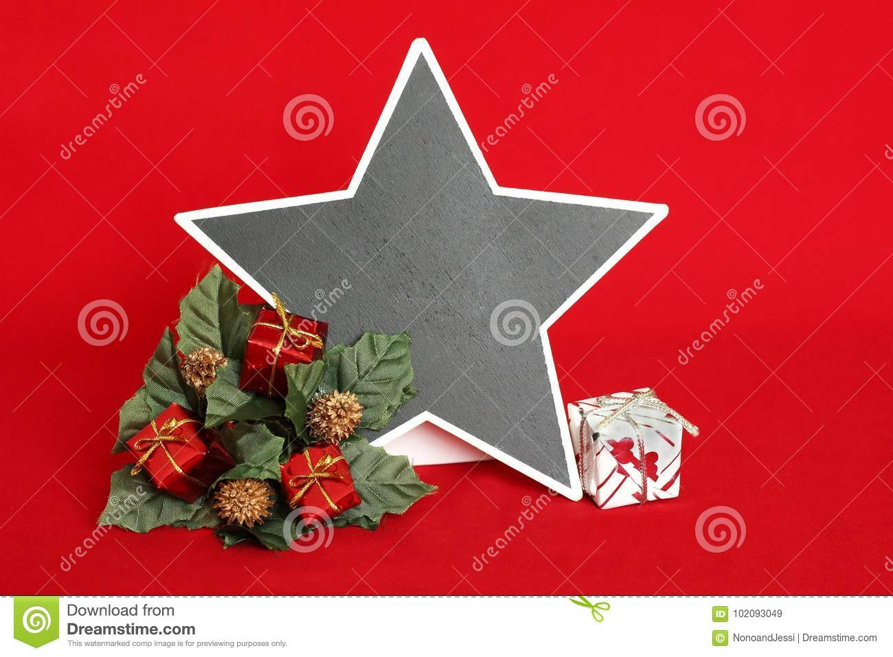 empty slate in the form of a star to write a message on a red background with red and white gifts placed on a wreath of fir for