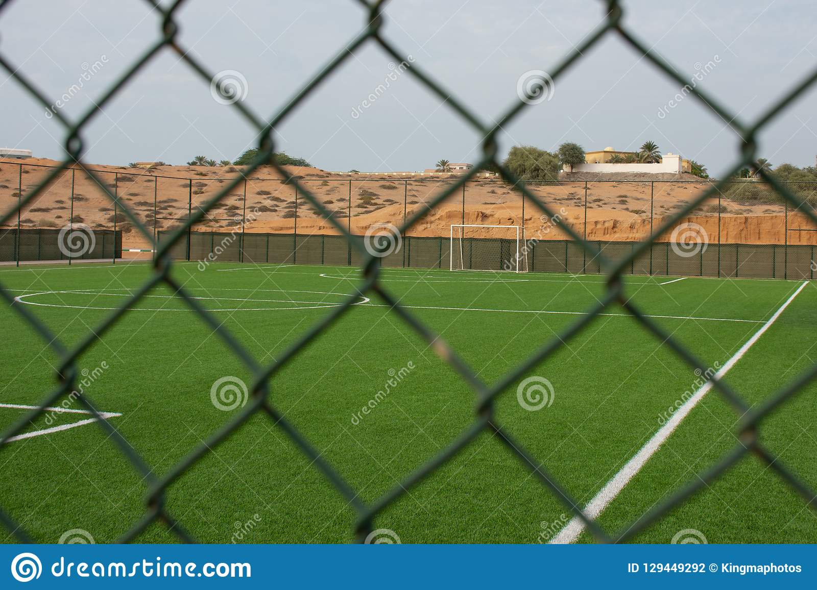 An empty soccer pitch viewed from outside the fence.