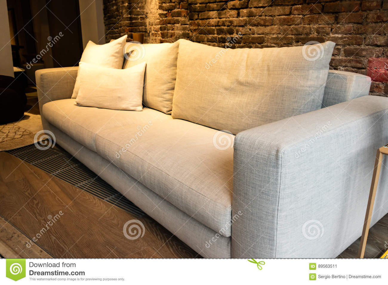 Store Display Of Empty Sofa With Pillows Under Yellow Indoor Lighting In  Room With Brick Wall