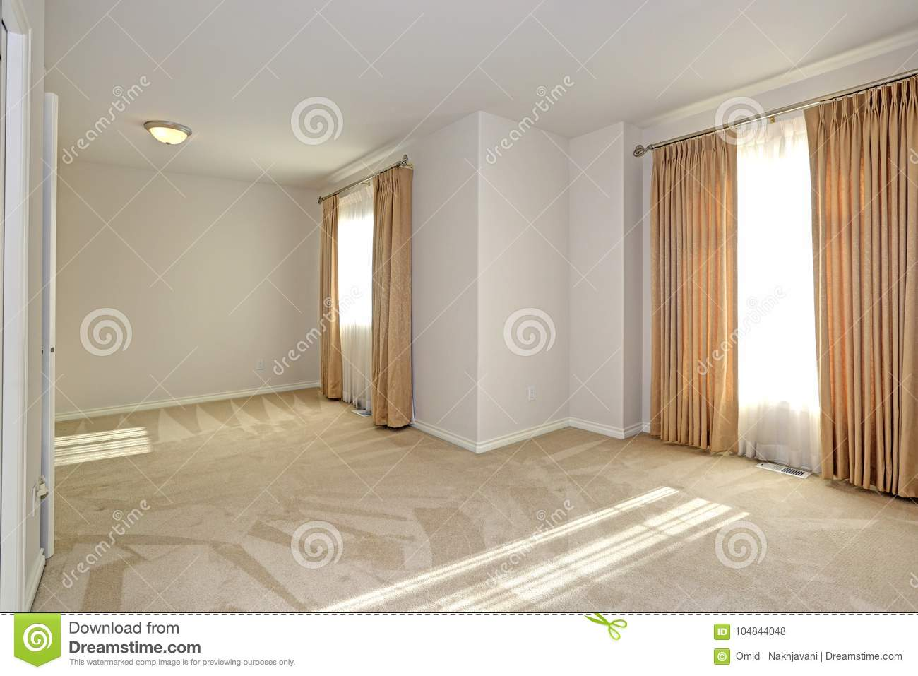 Empty Sun Filled Room With Carpet Floor And Cream Walls