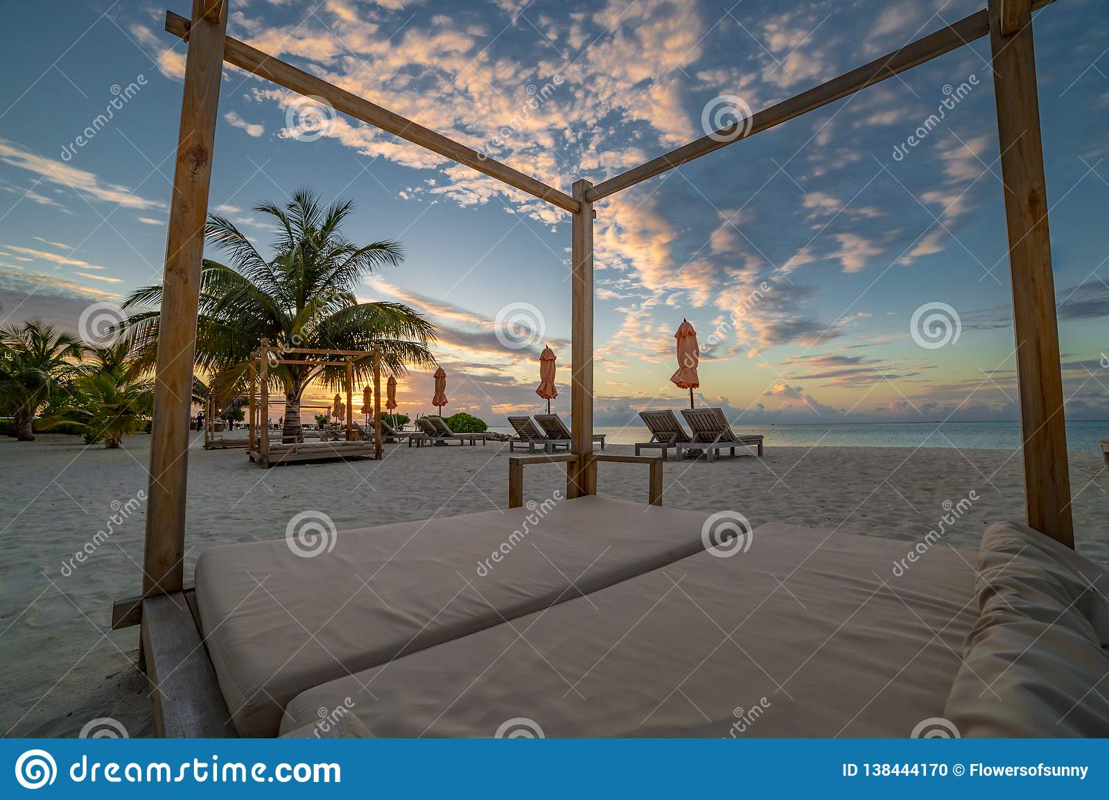 Beach canopy and sunset or sunrise colors on the sky and clouds. Amazing summer vacation moods on beach landscape