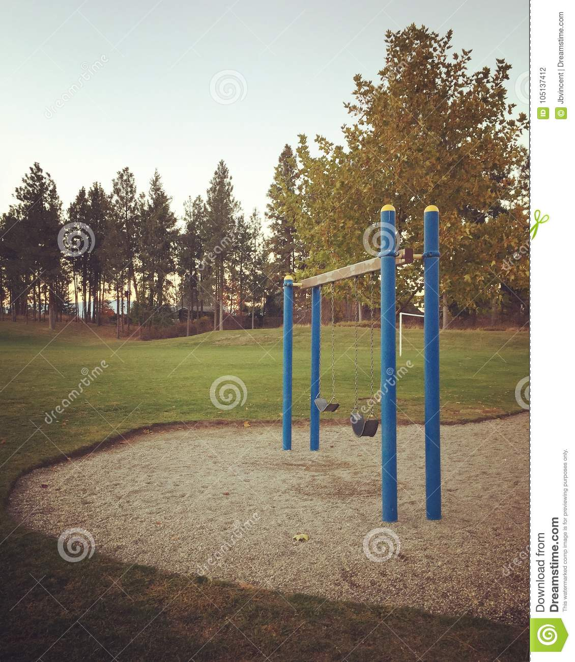 Empty Swingset In Field With Tall Trees Background Stock