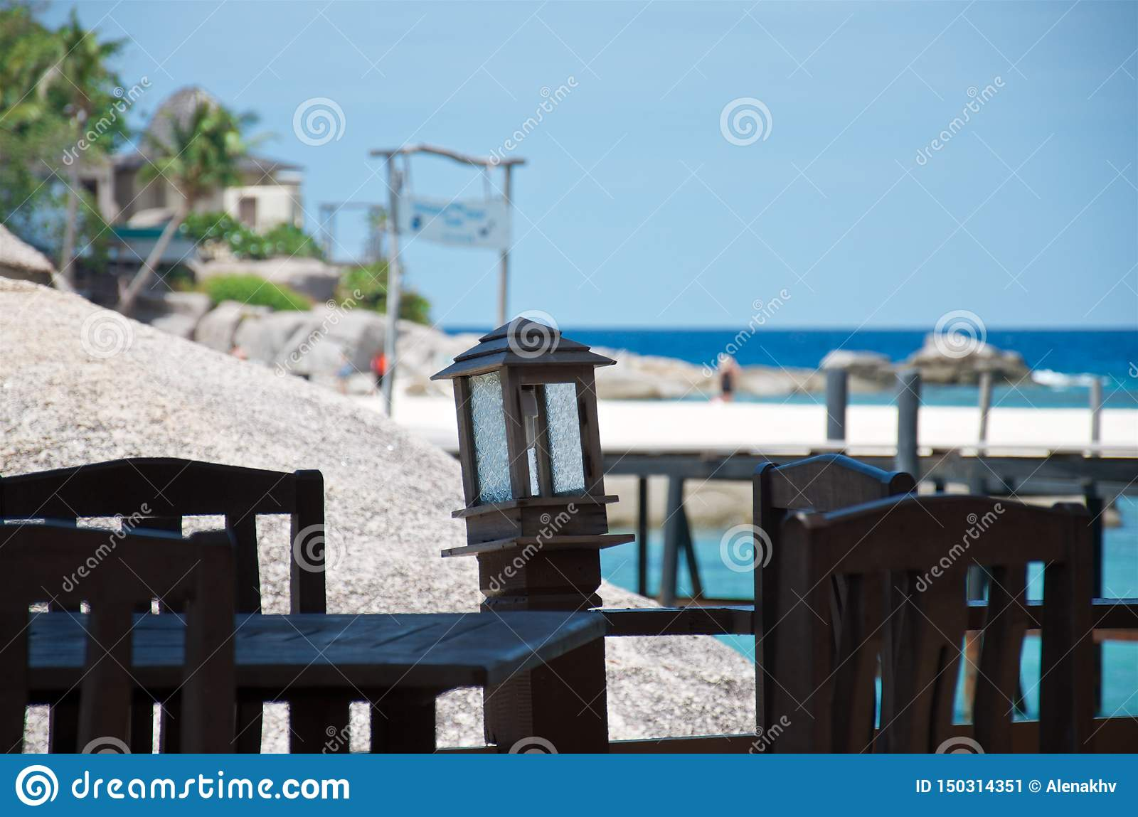 Empty table and chairs in a tropical beach restaurant