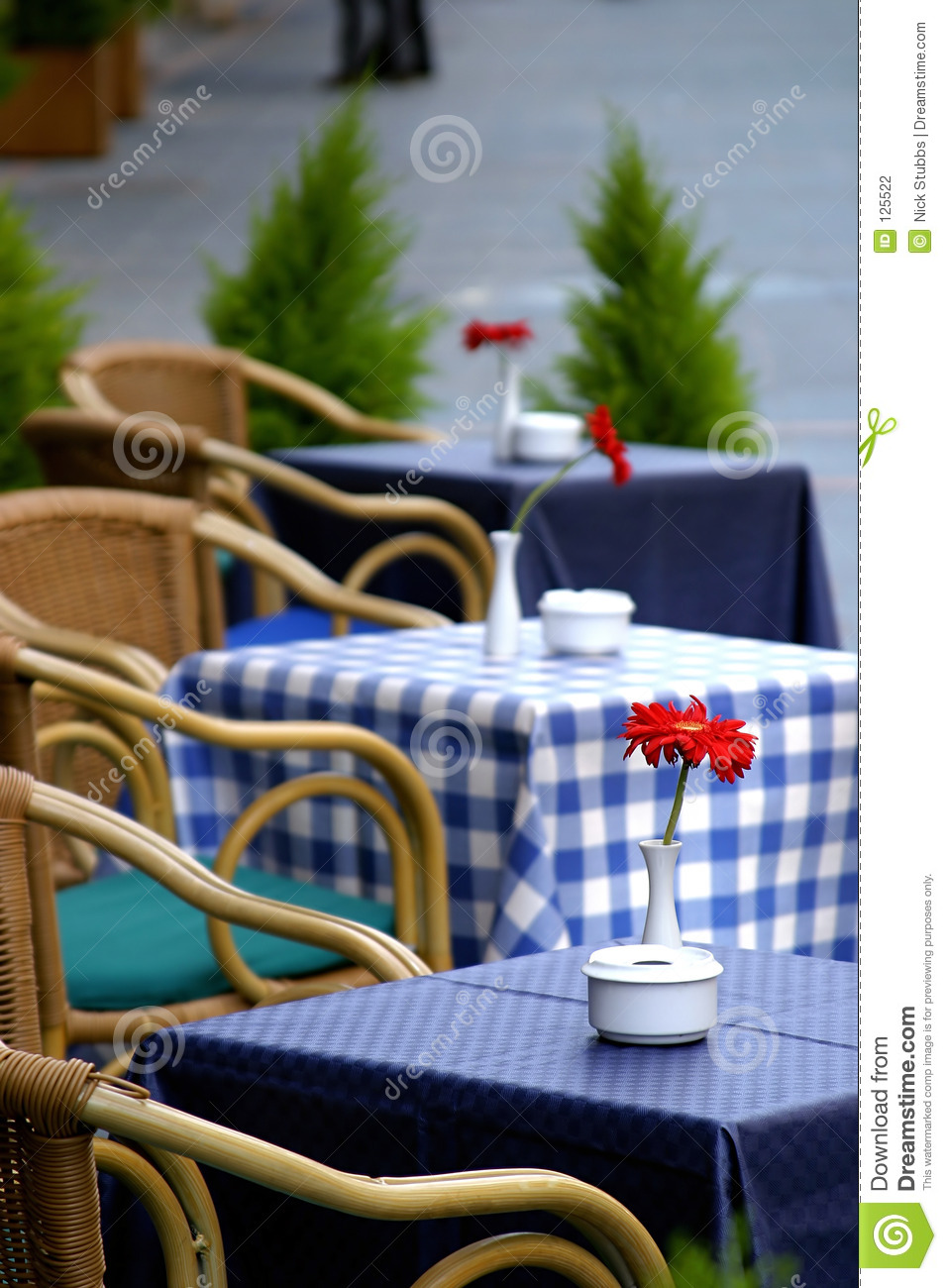 Empty tables with checkered table cloths on the street with roses on