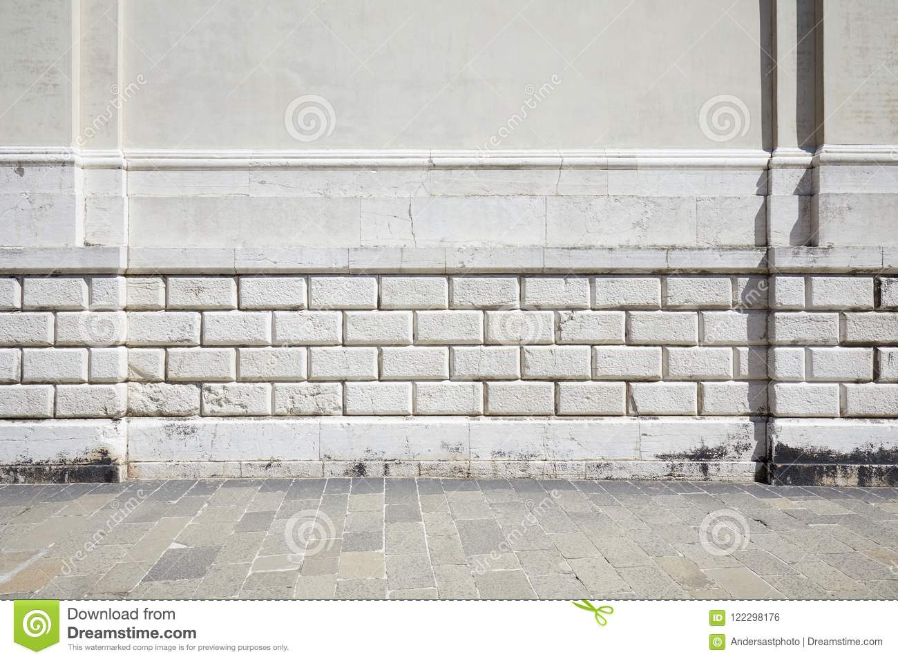 Empty tiled stone sidewalk and white ancient wall