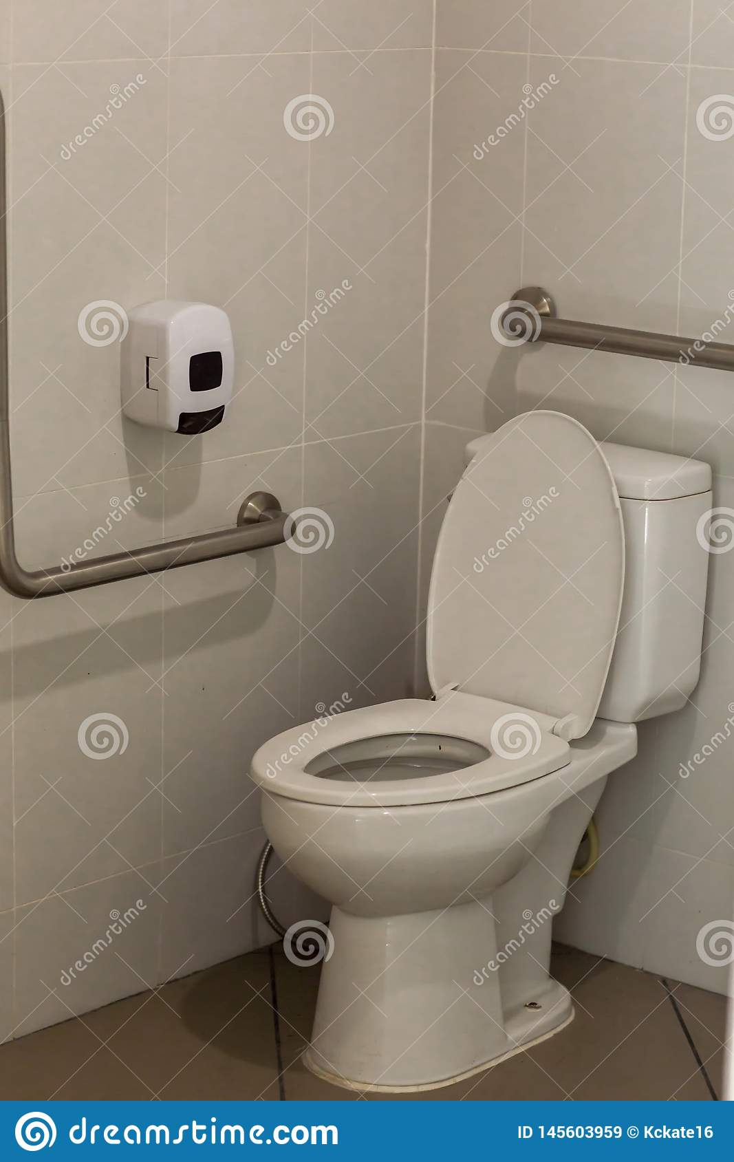 empty toilet for background. Toilet with handrails for the disabled. Focus on the lid of the toilet.