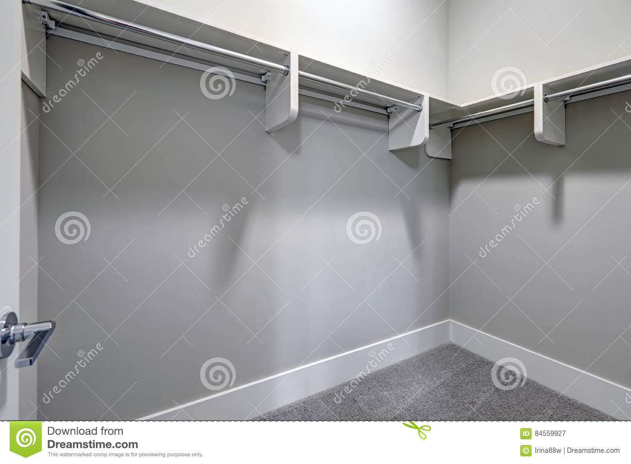 Empty Walk In Closet With Pale Gray Walls And Carpet Floor.
