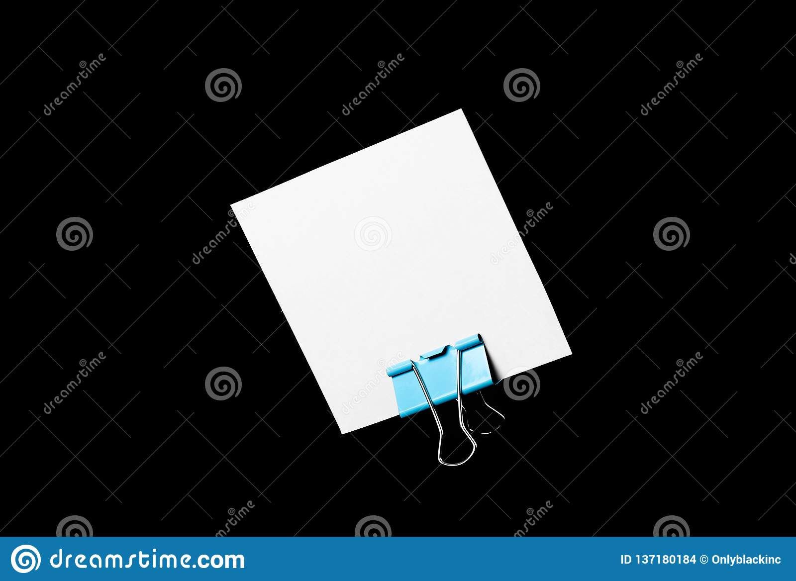 An empty white business card stands on a stationery clip. Close up. Isolated on black background