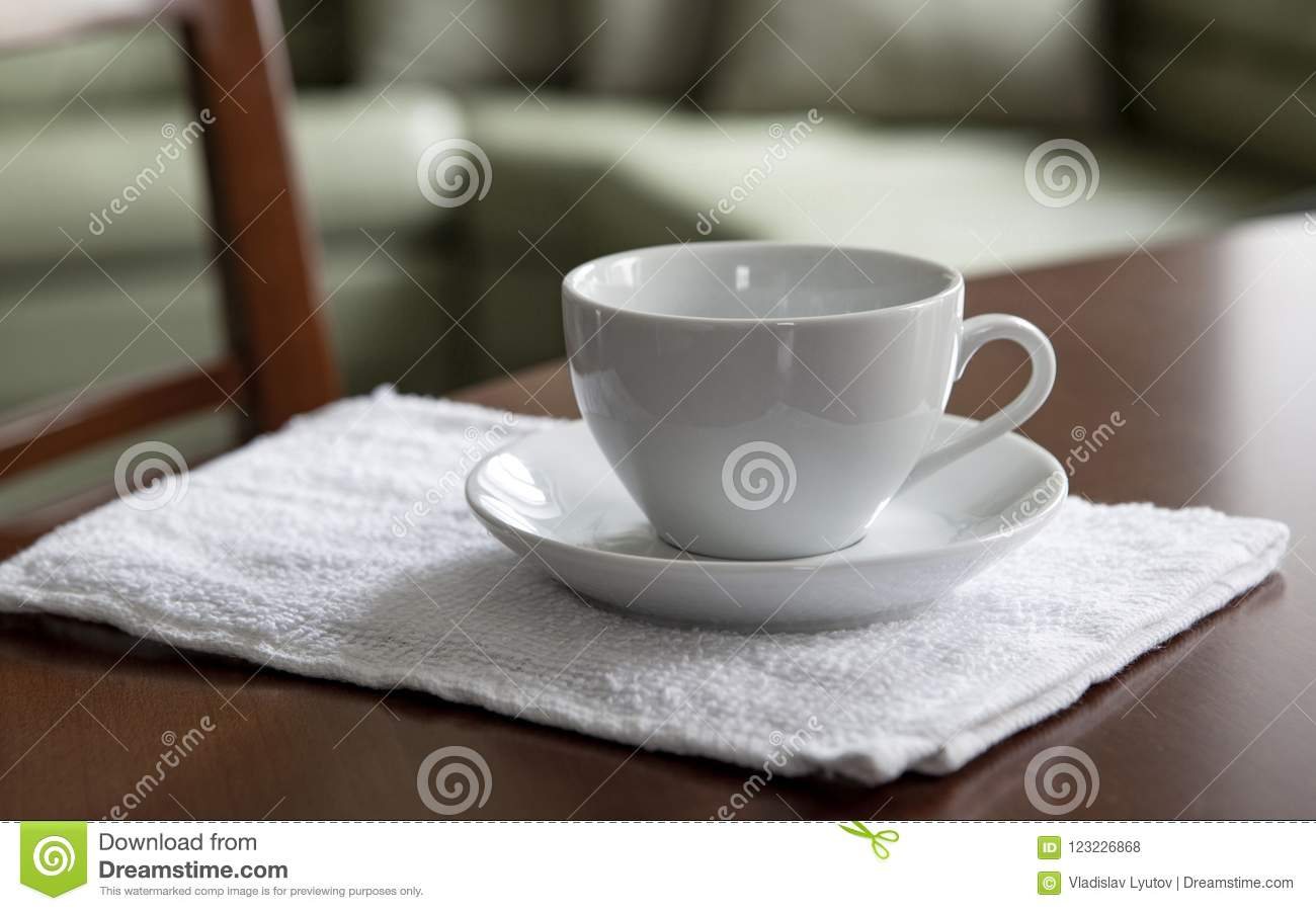 An Empty White Cup And A Saucer Stand On A Wooden Table Stock Photo