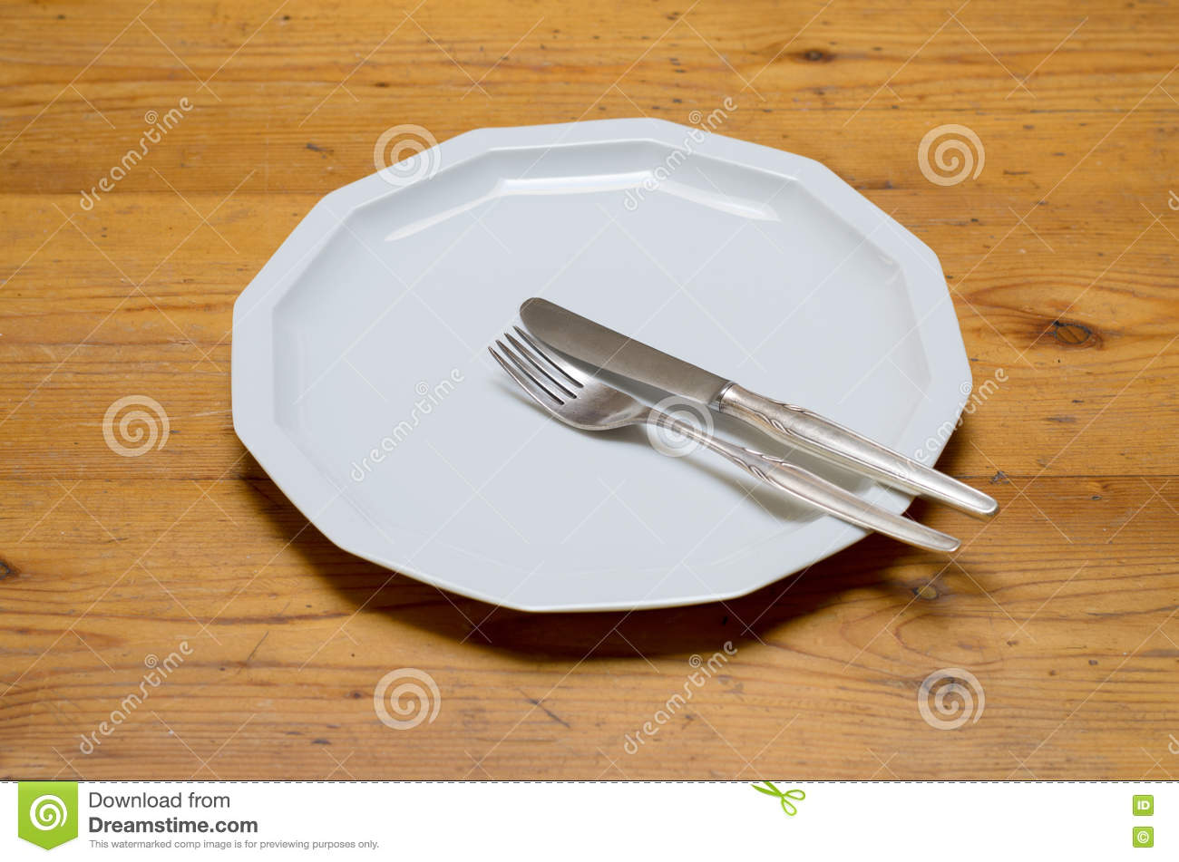 An empty white dish with knife and fork on a table - Empty White Dinner Plate With Knife And Fork
