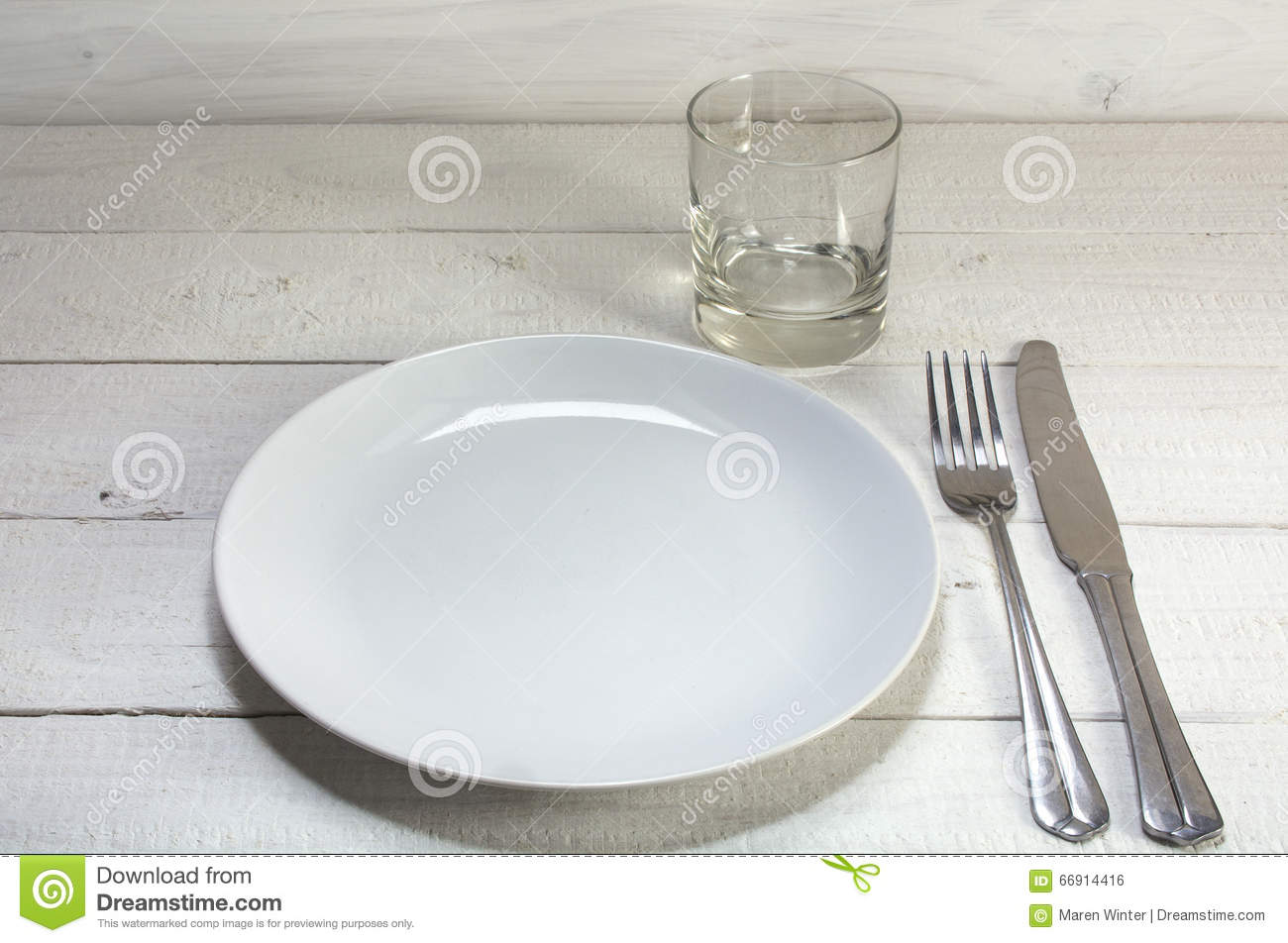 Empty White Plate With Knife Fork And Drinking Glass On A