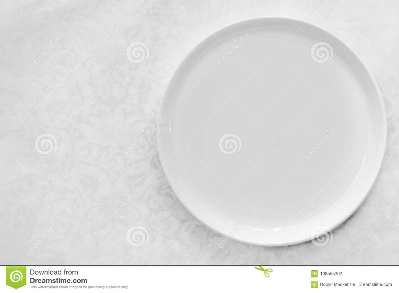 Empty White Plate over Brocade Tablecloth Top View