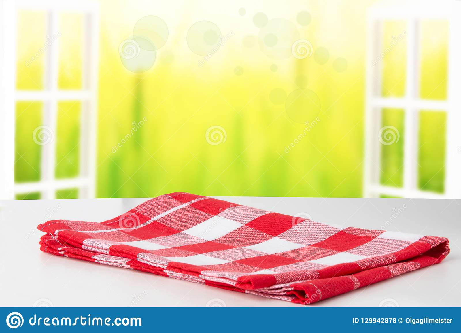 Empty white table top with red checkered napkin or tablecloth on