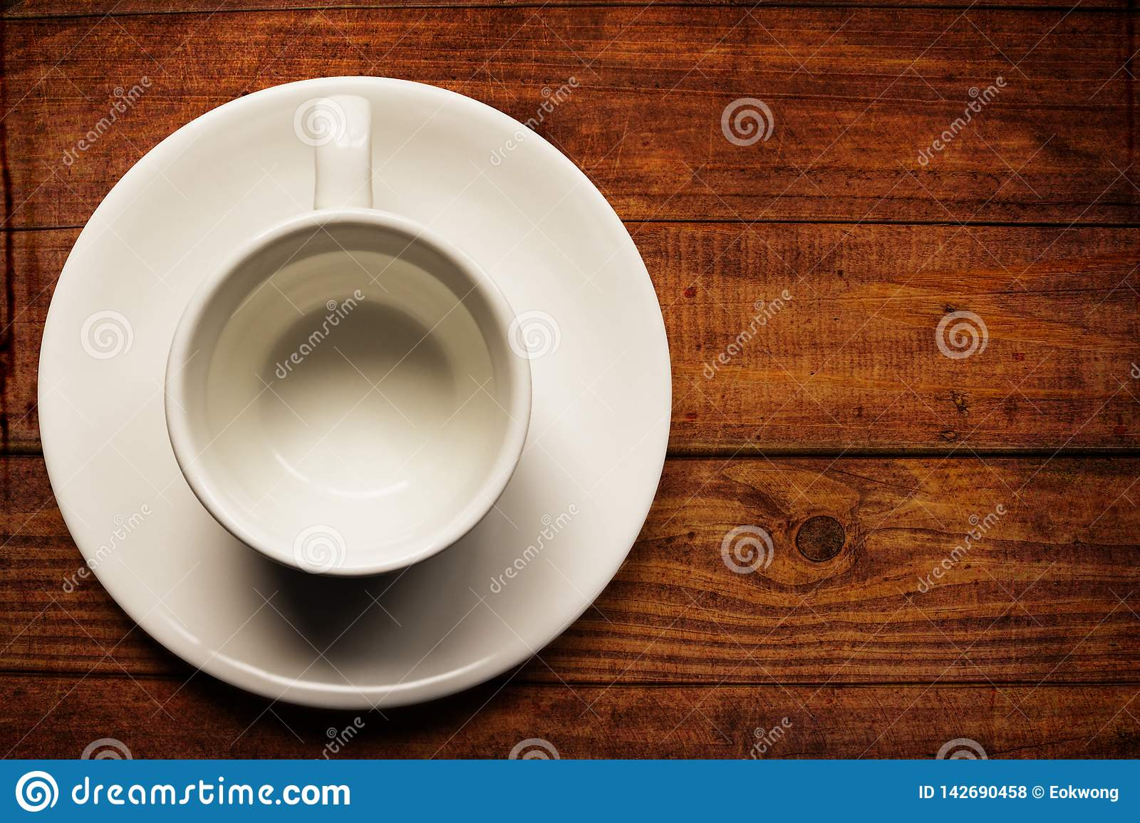 Empty white teacup and saucer on old wood texture background