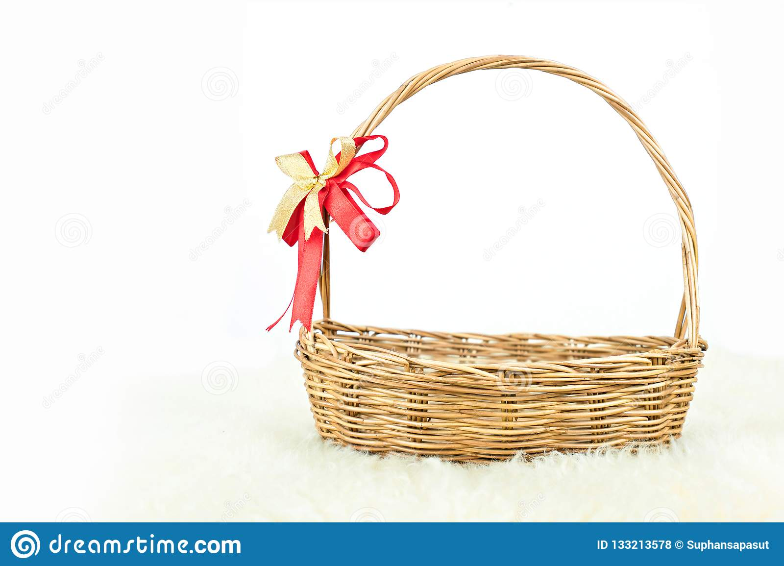 Empty wicker basket with red and gold ribbon isolated on white