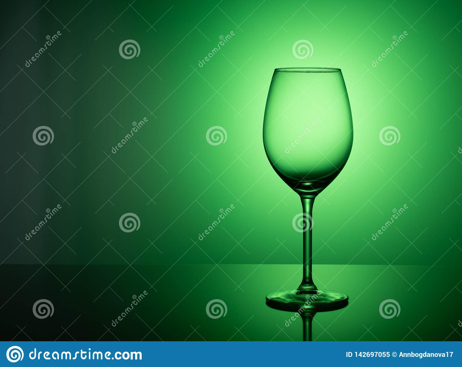 Empty glass stands on acrylic glass on a green background