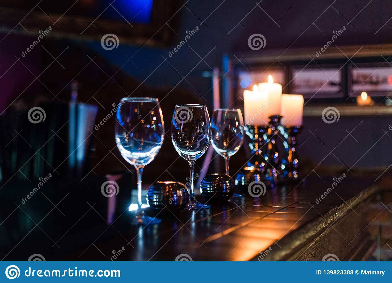 Empty wine glasses and candles with illumination lights background